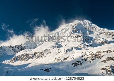 Strong wind blows snow away from a highlighted mountain peak - stock photo