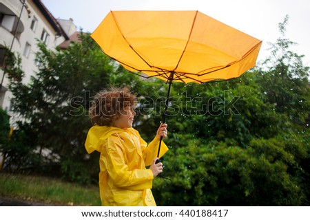Strong wind has wrest an umbrella in boy's hands. Strong wind has wrest an umbrella in boy's hands. But it is pleasant to the child. He to stand under warm rain and laughs. - stock photo