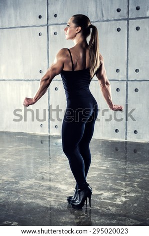 Strong woman bodybuilder standing in urban interior and looking aside. Contrast colors. - stock photo