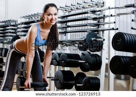 Strong woman chooses appropriate dumbbells in sport centre - stock photo