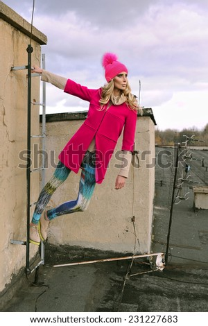 Strong woman in pink coat on roof - stock photo