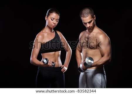 strong young couple working out with dumbbells. Shot in studio on a black background. - stock photo