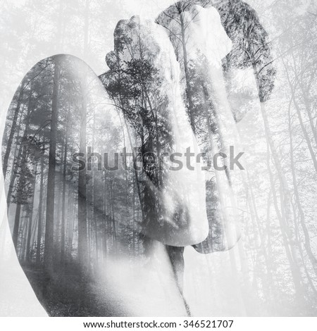 Strong young man hides behind his blocking hands, double exposure photo combined with wild forest landscape - stock photo