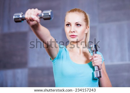 Strong young woman exercising with dumbbells at the gym doing shoulder muscles exercise - stock photo