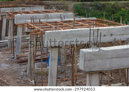 Structural beams and columns of the construction of a new concrete bridge in the rural areas. - stock photo