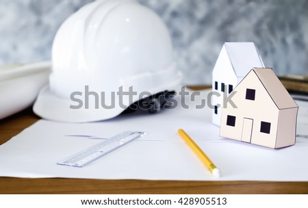 Structural engineer and architect working desktop with safety helmet and paper model houses. Construction engineering concept. - stock photo