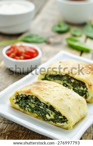 strudel with spinach and ricotta on a dark wood background. the toning. selective focus - stock photo