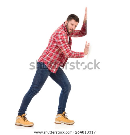 Struggle with a wall. Man in jeans and lumberjack shirt pushing a white banner. Full length studio shot isolated on white. - stock photo