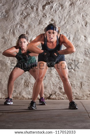 Struggling young white women sweating and lifting weights - stock photo