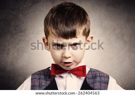 Stubborn,sad,upset  little boy,child  isolated over grey background.Facial expression - stock photo