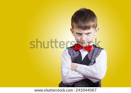Stubborn,sad,upset  little boy,child  isolated over yellow background.Facial expression - stock photo