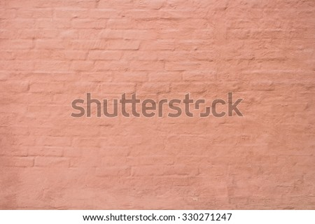 Stucco over brick wall. Plaster warm terracotta color on a brick wall. ?lose-up detail of rustic textured. Warmly toned mediterranean facade, wall with painted structured plastering. - stock photo