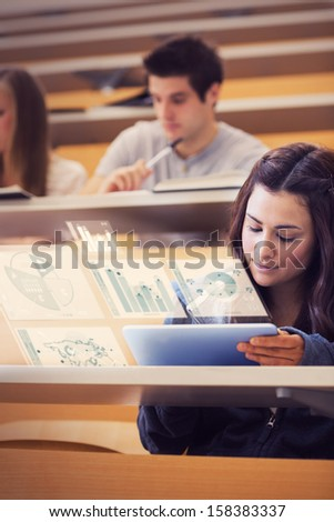 Student analyzing graphs on her digital tablet computer in lecture hall - stock photo