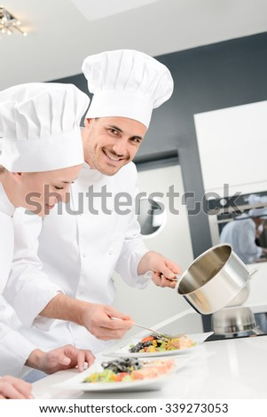 student and teacher in a professional cook school kitchen preparing a plate for restaurant - stock photo
