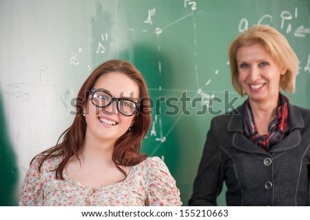 Student and teacher standing in front of a blackboard - stock photo