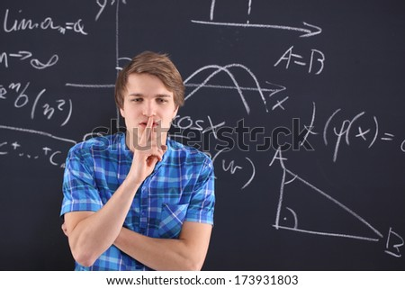 Student at the blackboard . Student at blackboard background saved mathematical formulas  - stock photo