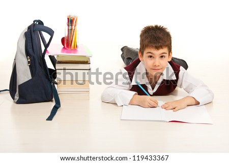 Student boy lying on the floor home and doing  homework - stock photo