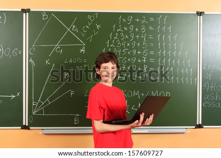 Student boy standing with his laptop over blackboard at a classroom. Education. - stock photo