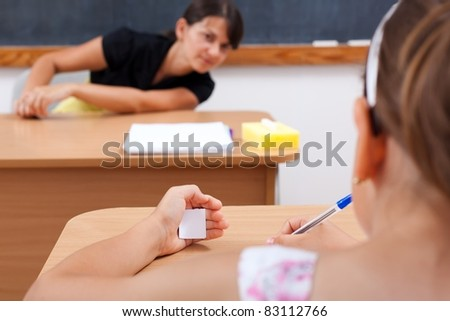 Student cheating while writing test, teacher is looking at her - stock photo
