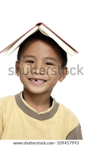 Student child with a book over his head isolated over white background - stock photo