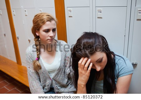 Student comforting her friend while sitting on a bench - stock photo