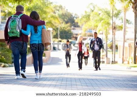 Student Couple Walking Outdoors On University Campus - stock photo