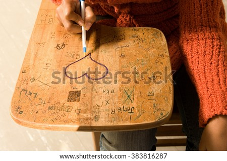 Student drawing a heart on her desk - stock photo