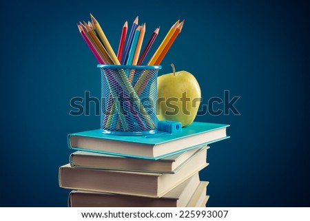 Student equipment with pile of books, apple and color pencils, back to school concept. - stock photo