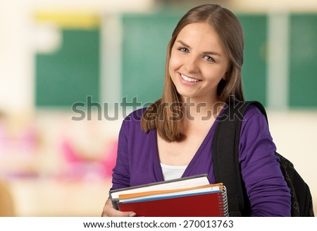 Student. Female student holding books and bag in campus - stock photo