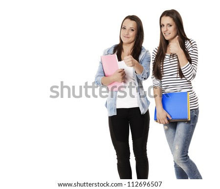 student female teenagers with notepads showing thumbs up on white background - stock photo