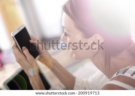 Student girl in class using smartphone - stock photo