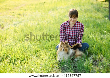 Student girl learning in nature with dog in the park on the grass - stock photo