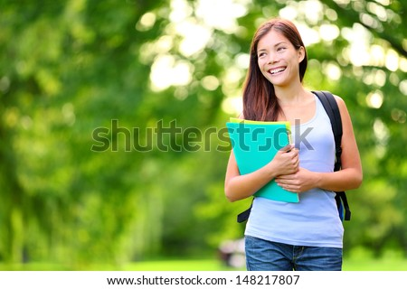 Student girl outdoor in park smiling happy going back to school. Asian female college or university student. Mixed race Asian / Caucasian young woman model wearing school bag holding books. - stock photo
