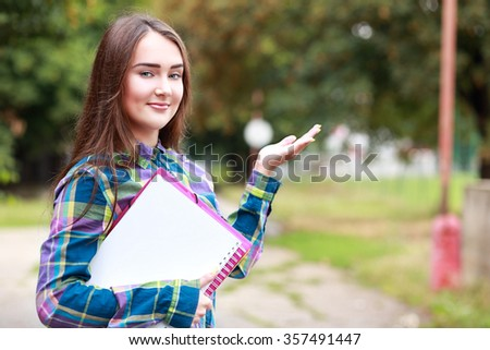 Student girl outdoors going back to school and smiling presenting copyspace - stock photo