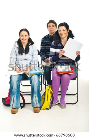 Student girl showing empty notebook with A+ in a circle in classroom and her colleagues smiling at camera - stock photo