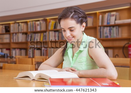 Student girl studying at the university library - stock photo