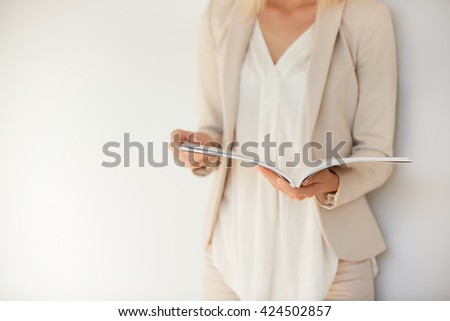 Student girl wearing white shirt and beige suit preparing for final exams at university. Attractive blonde female entrepreneur reading women's magazine while relaxing in cafe after working day   - stock photo