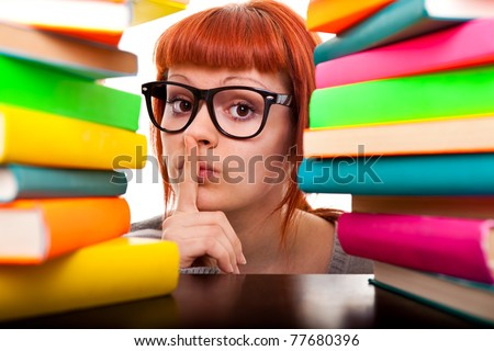 student girl with finger on mouth, peeking between stack of books,  isolated - stock photo