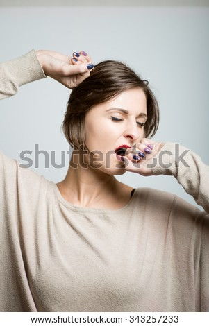 student girl yawning at work. office manager. studio photo on a gray background - stock photo