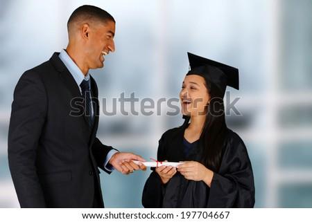 Student graduating standing by her teacherat school - stock photo