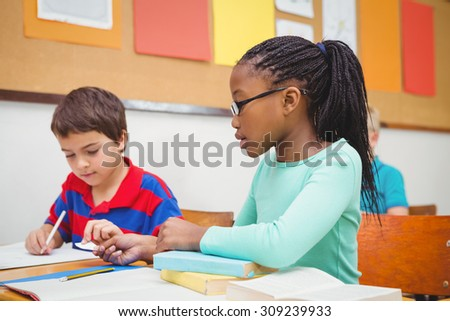 Student helping fellow student in class at the elementary school - stock photo