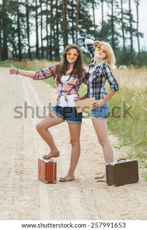 Student hitchhikers wearing sunglasses and holding cardboard - stock photo