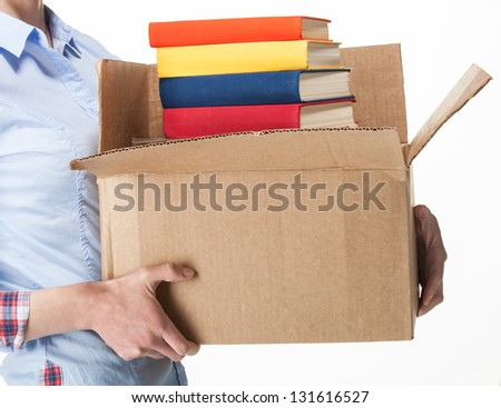 Student holding a big box with stack of books; isolated on white - stock photo