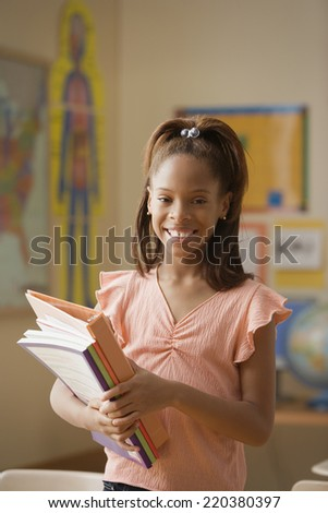 Student holding her books and smiling for the camera - stock photo