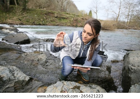 Student in biology taking sample of natural water - stock photo