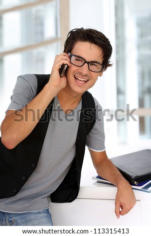 Student in building talking on mobile phone - stock photo