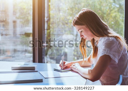 student in classroom during exam - stock photo