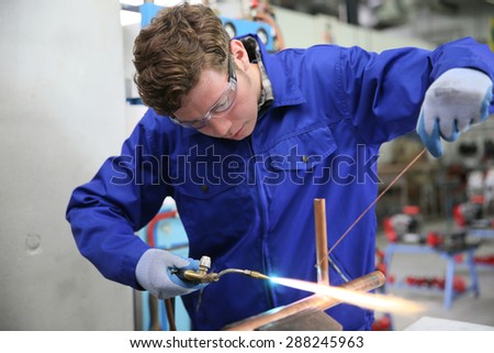 student in plumbing professional training, working on copper - stock photo