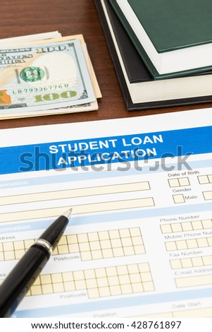 Student loan application form with pen, dollar banknote, and text book - stock photo