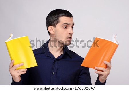 Student looking amazed at the books. Surprised teacher. Man in dark blue shirt holding two books with orange and yellow blank covers. - stock photo